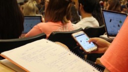 A student is on their phone using Squarecap for a poll during class