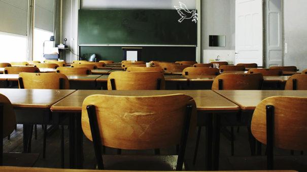 A chalk-drawn dove flies off of an empty blackboard in an empty classroom