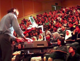 A professor stands at the podium as he teaches a large class full of students.