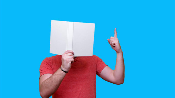 A professor holds an open notebook in front of his face and points to the ceiling as if making a point.
