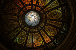 A picture of a stained glass ceiling with the hand-cursor icon hovering over it