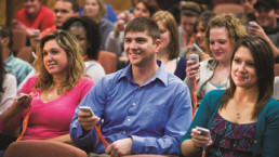 Photo of students answering a polling question with their phones
