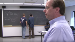 MIT Professor Steven Hall watches students working at a chalkboard